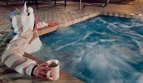 Rae Harris in a hot tub while wearing a unicorn costume