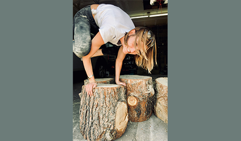 Rae Harris doing a hand stand on a tree stump